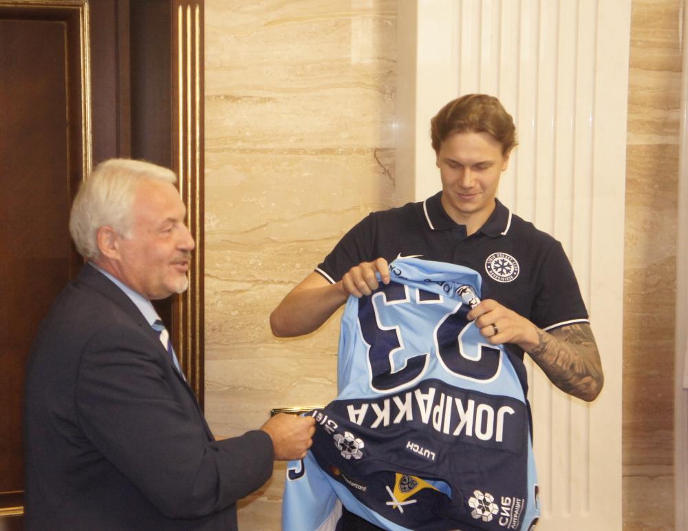 Кирилл Фастовский вручает свитер защитнику Юрки Йокипакке -- недавнему приобретению «Сибири»