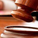 Судья бьет молотком в зале суда
