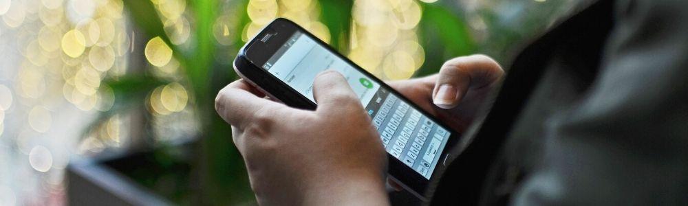 Человек набирает на мобильном телефоне сообщение