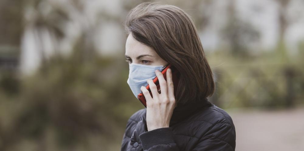 девушка в маске с телефоном