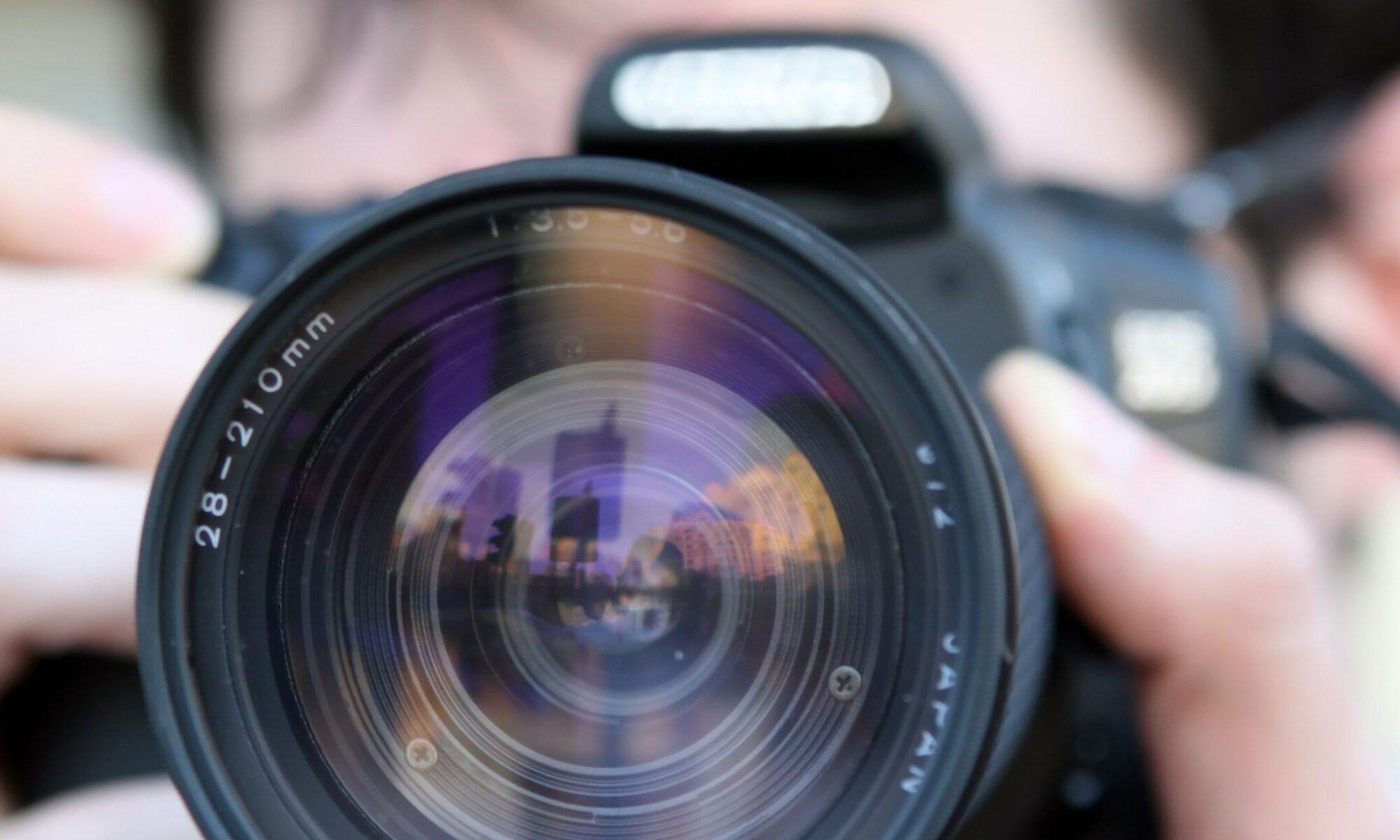 объектив фотоаппарата в руках