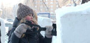 девушка вытачивает из снега фигуру